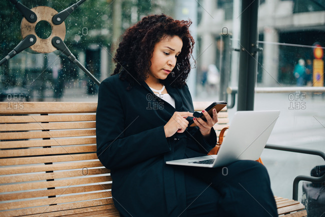 Mid adult businesswoman using mobile phone while sitting with laptop at bus shelter