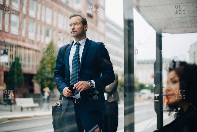 Businessman and businesswoman waiting at bus stop seen from glass
