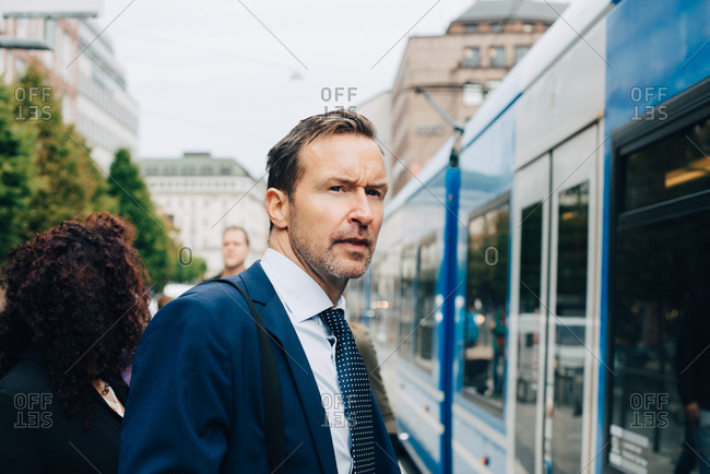 Mature businessman standing by cable car in city