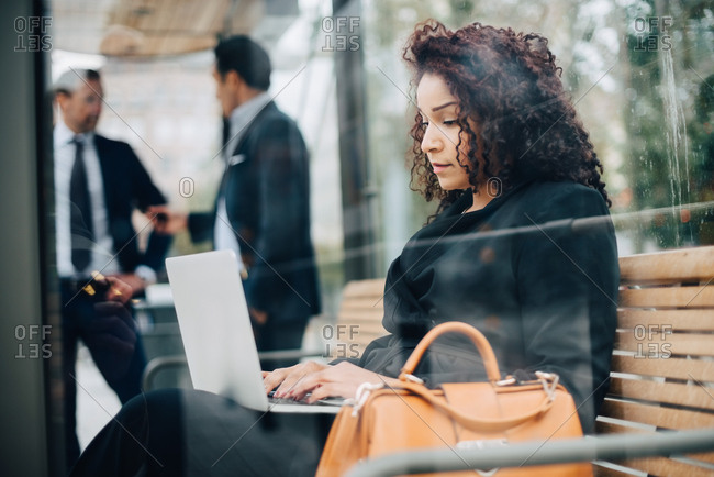 Side view of mid adult businesswoman using laptop sitting at bus shelter seen from glass