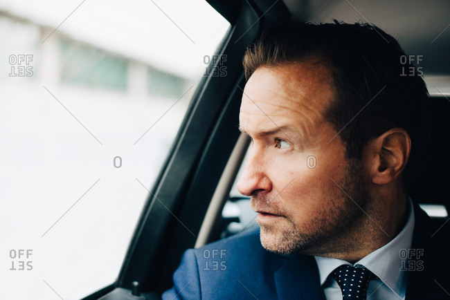 Mature businessman looking away through window while sitting taxi in city