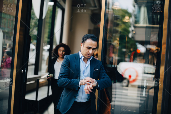 Mature businessman looking at wristwatch while walking against glass