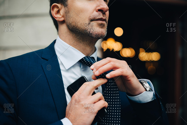 Midsection of businessman adjusting necktie while holding mobile phone