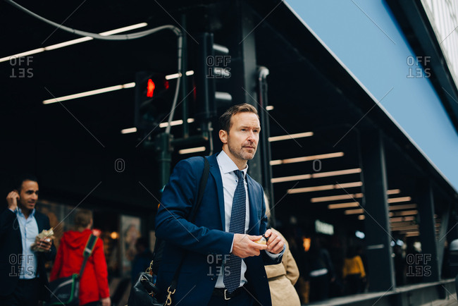 Mature businessman looking away while walking in city
