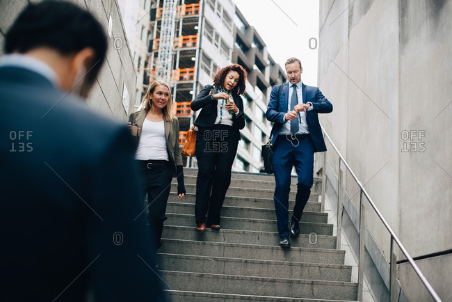 Low angle view of business colleagues moving down stairs in city