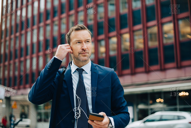 Mature businessman positioning in-ear headphones while looking away against buildings in city