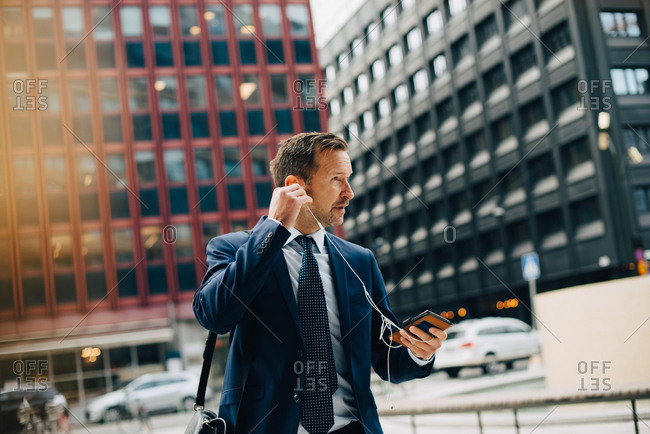 Mature businessman positioning in-ear headphones while walking against buildings in city