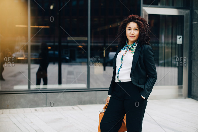 Portrait of confident businesswoman standing against building in city