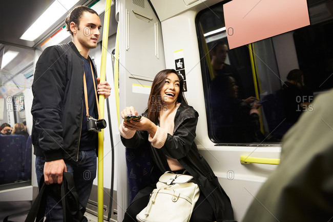 Happy woman holding mobile phone while sitting by man in train
