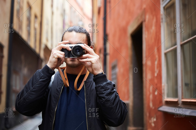 Man photographing through camera while standing against buildings