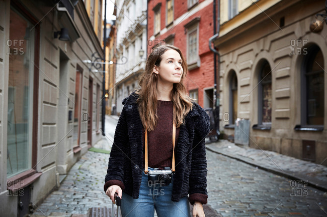 Young woman with camera looking away while standing in alley