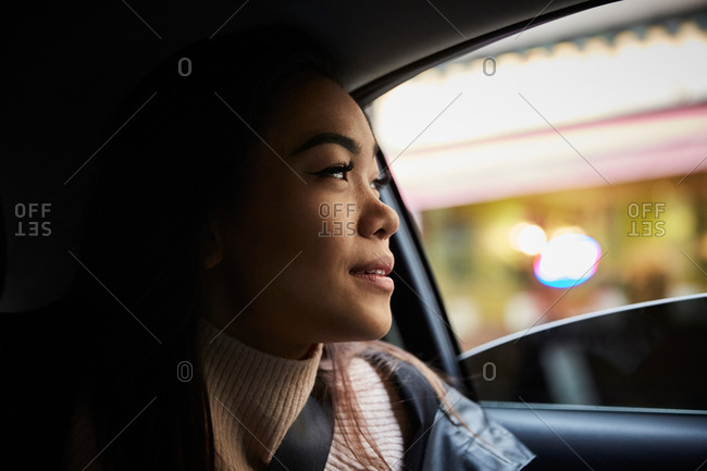 Thoughtful young woman looking through window while sitting in car