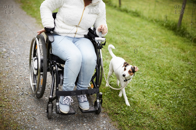 Low section of disabled woman in wheelchair with dog on dirt road