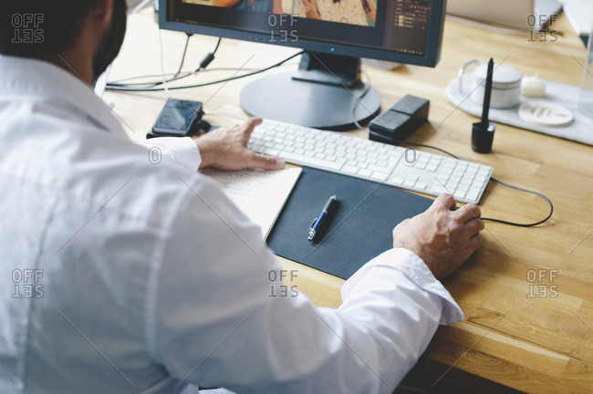 High angle view of businessman using computer at desk in creative office