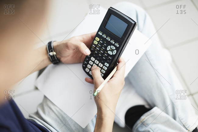 Cropped image of man using calculator while studying at laundromat