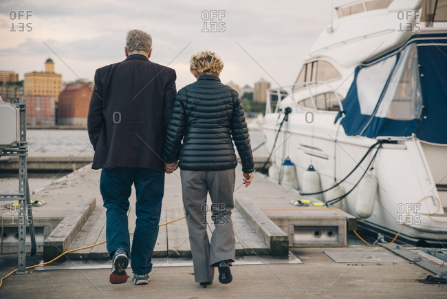 Full length rear view of senior couple holding hands while walking on pier at harbor