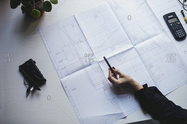 Cropped hand of businesswoman with blueprint on desk