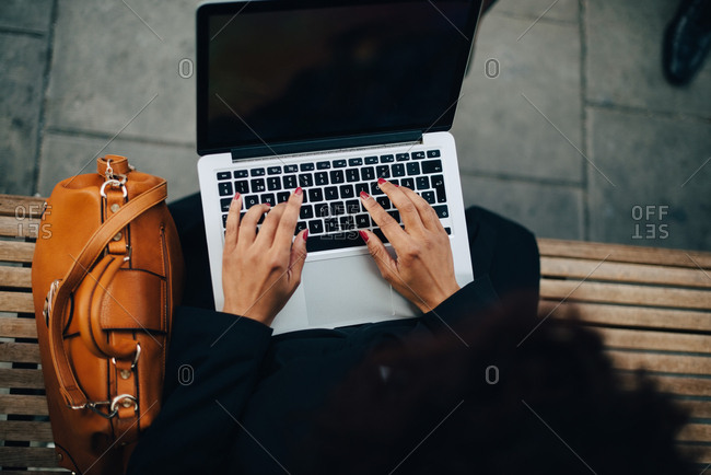 High angle view of businesswoman typing on laptop while sitting on bench at bus shelter