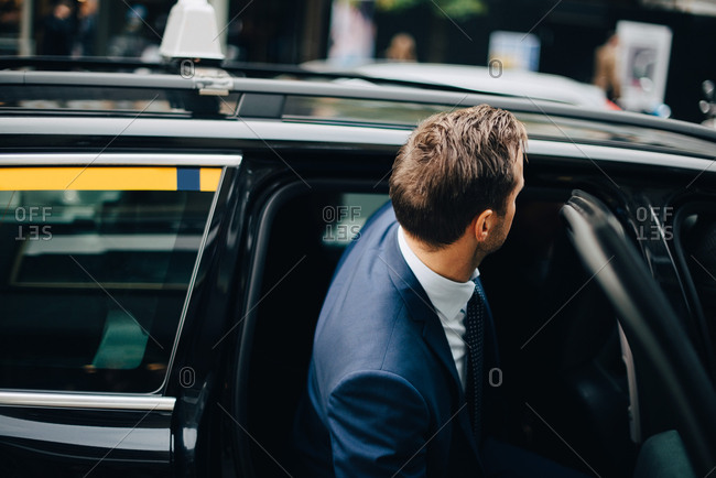 Side view of businessman entering taxi in city