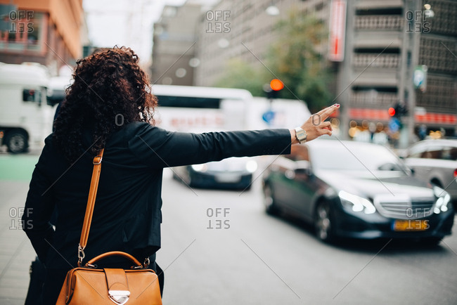 Rear view of mid adult businesswoman hailing taxi on street in city