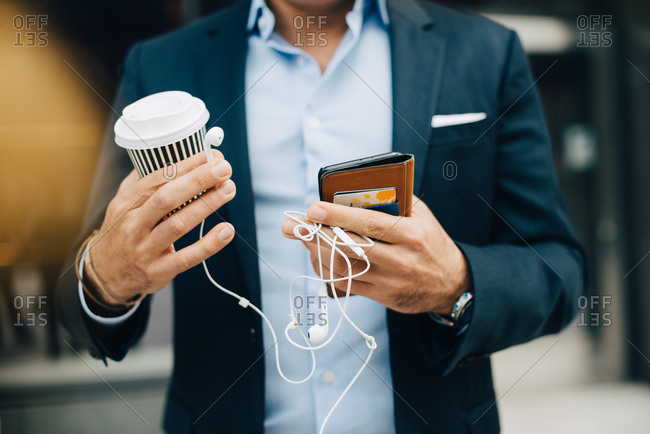 Midsection of businessman holding smart phone with disposable coffee cup and in-ear headphones while standing in city