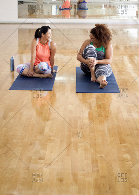 Full length of female friends talking while sitting on exercise mats in gym
