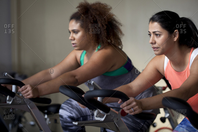 Female friends exercising on exercise bikes in gym