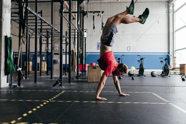 Man walking on hands in gym