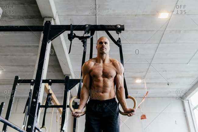 Shirtless muscular sportsman hanging on flying rings working out in gym.