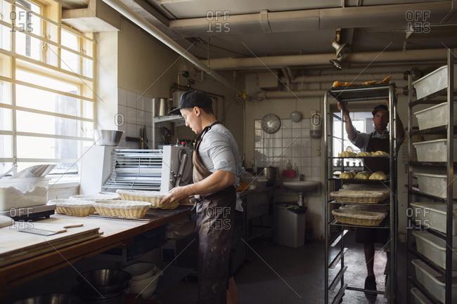 Bakers preparing dough in kitchen