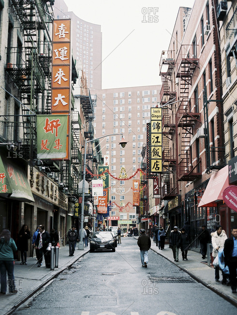 Chinatown, New York - December 15, 2017: People walking through side street