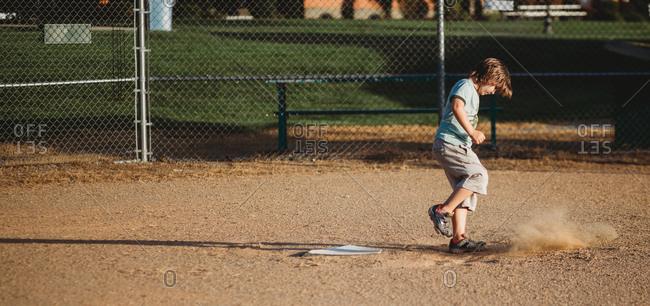 Boy kicking ground in baseball field