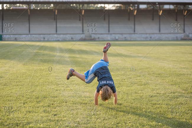 Boy doing cartwheels on athletic field