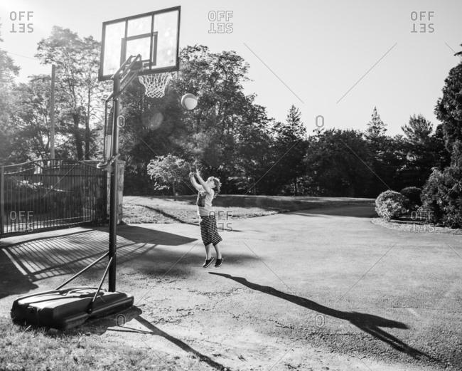 Kid shooting a basket in driveway