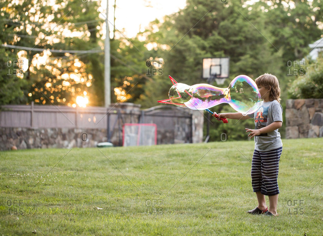 Boy playing with large bubbles in backyard