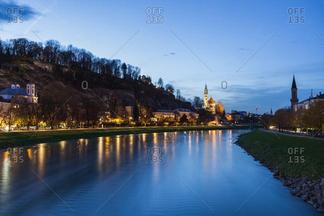 Austria, Salzburg, River and illuminated riverbank at dusk