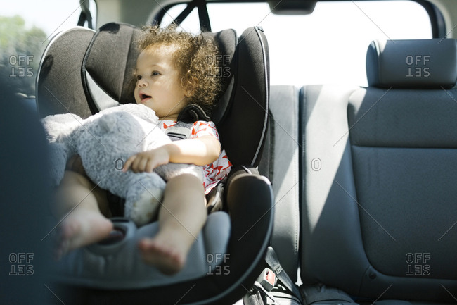 Girl (12-17) sitting on car seat and holding plush toy