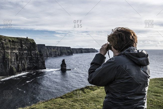 Ireland, Clare County, Woman looking through binoculars on Cliffs of Moher