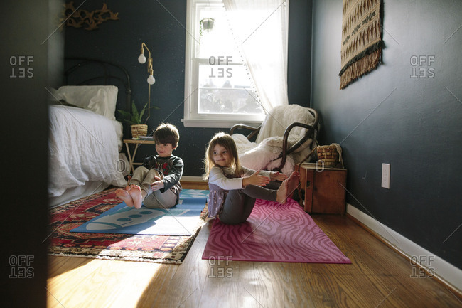 Children sitting on yoga mats stretching together