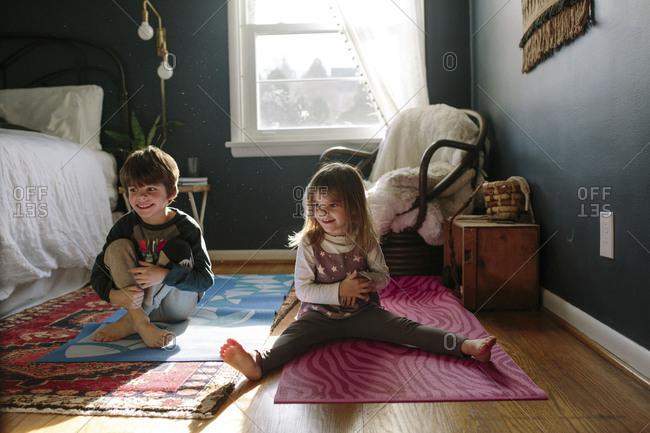 Smiling children sitting on yoga mats together