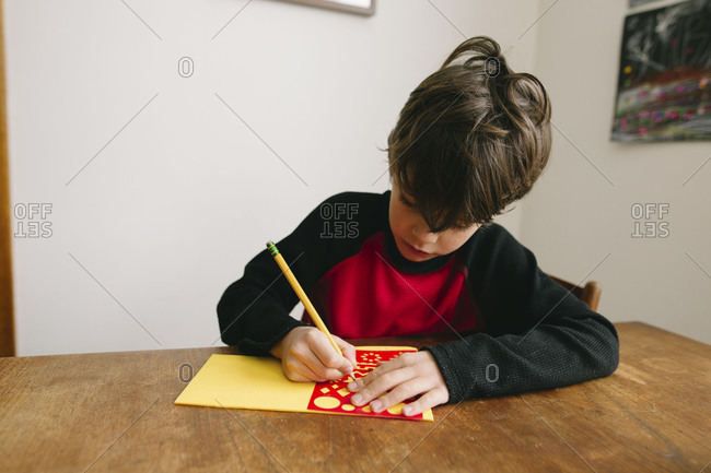 Boy drawing on foam sheet using stencils