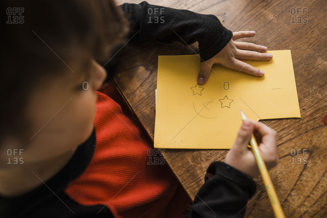 Boy drawing a picture of a face with star-shaped eyes