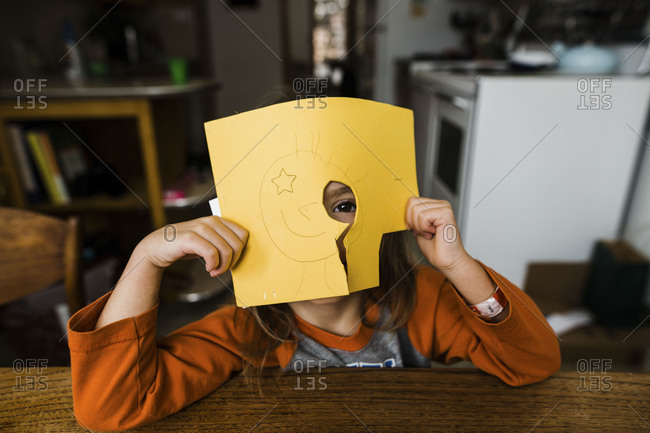 Girl looking through hole cut in foam sheet