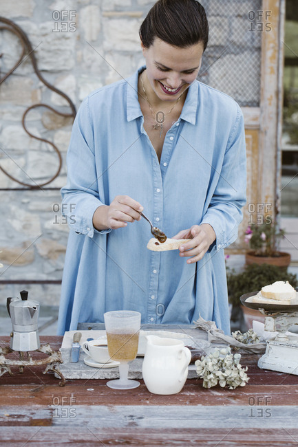 Italy- laughing woman putting jam on slice of bread on terrace