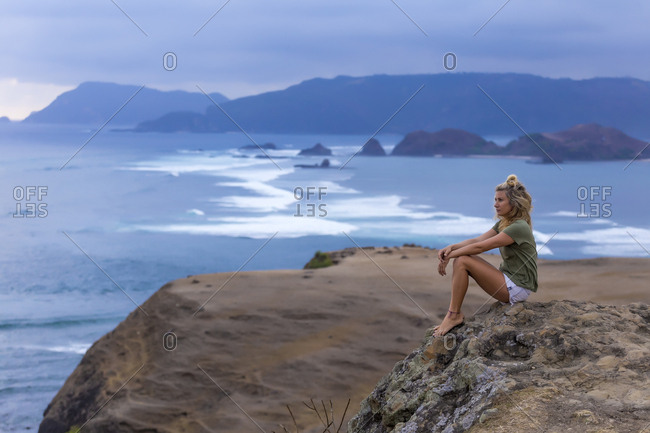 Indonesia- Lombok- woman sitting at the coast looking at view