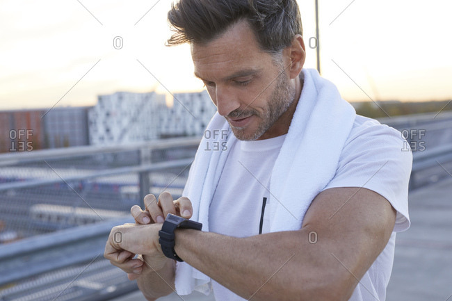 Athlete in the city looking on smart watch