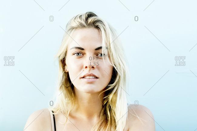Portrait of blond woman against light blue sky