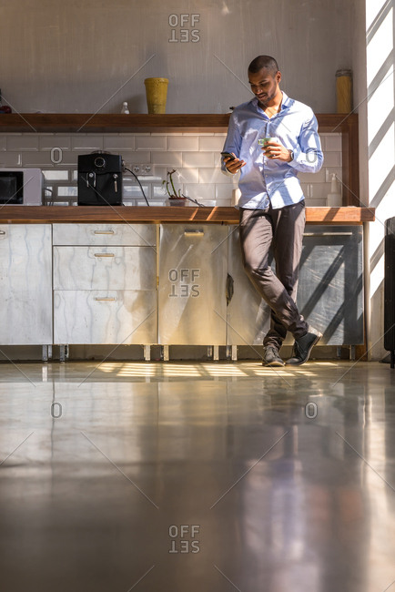 Young entrepreneur standing in company kitchen- drinking coffee- using smartphone