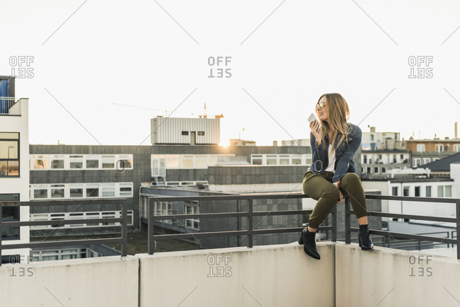 Smiling young woman in the city using cell phone on railing