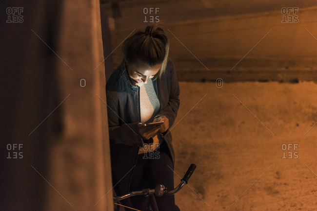 Young woman in the city checking cell phone at night